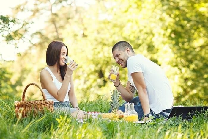 Pärchen beim Sommer-Picknick auf grüner Wiese